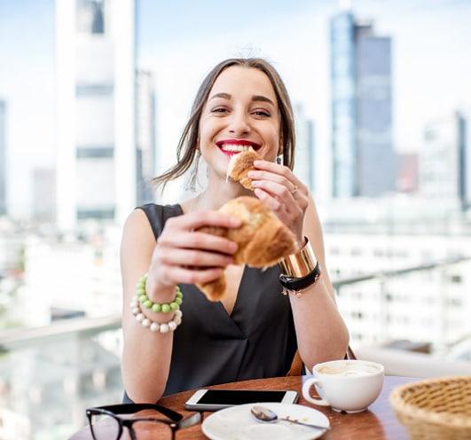 dame frühstückt mit frankfurter skyline im hintergrund