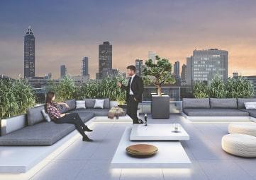 Mann und Frau treffen sich auf der studiomuc Dachterrasse mit Frankfurter Skyline im Hintergrund